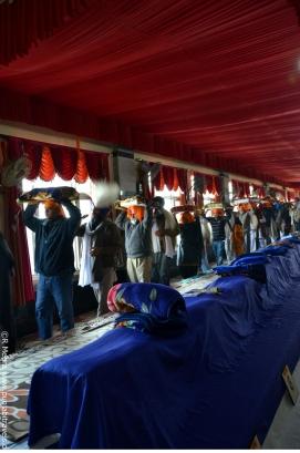 Die Guru Granth Sahib wird in einen Nebenraum getragen.